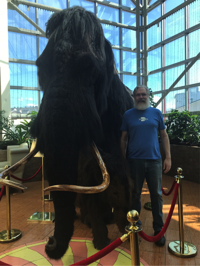 George Church poses with a woolly mammoth in a hotel lobby